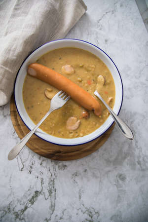 Hearty German yellow split pea soup stew with Bockwurst sausages in enamel dish on wooden board and light marble background Standard-Bild