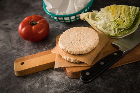 Vegan vegetarian burger patty raw on wooden cutting board and knife with iceberg lettuce and tomato on dark concrete background Standard-Bild