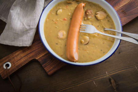 Hearty German yellow split pea soup stew with Bockwurst sausages in enamel dish on wooden board and dark background