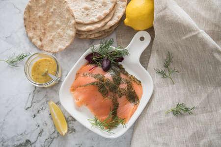 Gravlax a raw, marinated graved salmon with dill on plate with crispbread, Scandinavian mustard sauce, lemon and linen towel on light marble background Standard-Bild