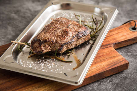 Medium rare fried beef steak with rosemary and salt on stainless steel tray, wooden board and dark stone background Stock fotó