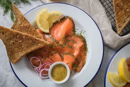 Gravlax a raw, marinated graved salmon with dill on enamel plate with toast bread, Scandinavian mustard sauce, lemon, onion rings and linen towel on light marble background