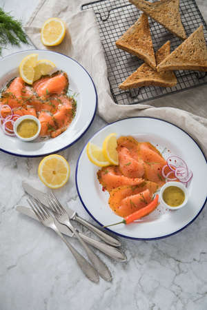 Classic and Asian style Gravlax a raw, marinated graved salmon with lemongras, chili, dill with toast bread, Scandinavian mustard sauce, dill, lemon, onion rings on enamel plate, linen towel and light marble background Standard-Bild