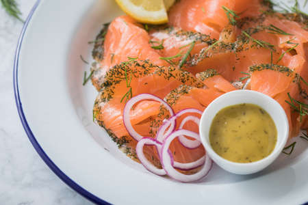 Gravlax a raw, marinated graved salmon with dill on enamel plate with Scandinavian mustard sauce, lemon, onion rings and linen towel on light marble background