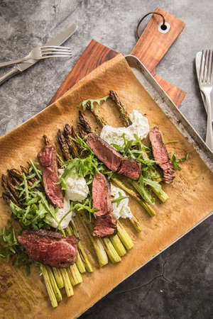Roasted green asparagus with medium rare beef steak, rocked salad, buffalo mozzarella cheese and olive oil on baking tray, wooden board, cutlery and rustic dark stone background