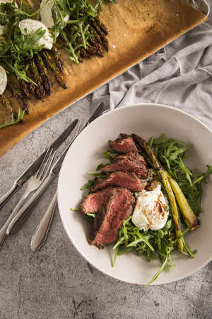 Roasted green asparagus with medium rare beef steak, rocked salad, buffalo mozzarella cheese and balsamic in bowl and baking tray, cutlery and rustic stone background