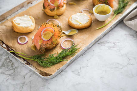 Gravlax a raw, marinated graved salmon with dill on bred roll bun with cream cheese, Scandinavian mustard sauce, onion rings on tray with baking paper and light marble background Standard-Bild