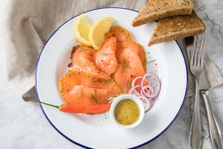 Asian style Gravlax a raw, marinated graved salmon with lemongrass and chili on enamel plate with toast bread, Scandinavian mustard sauce, dill, lemon, onion rings and linen towel on light marble background