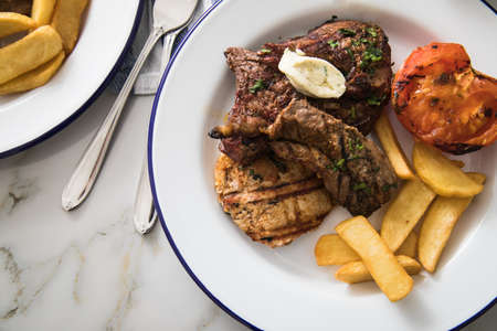 Grill platter with beef steak, chicken and lamp filet, steakhouse fries, grilled tomato, herb butter on emailed white blue plate and light marble background Standard-Bild
