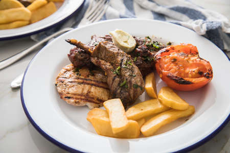 Grill platter with beef steak, chicken and lamp filet, steakhouse fries, grilled tomato, herb butter on emailed white blue plate, kitchen towel and light marble background