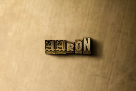 letterpress type: AARON - close-up of grungy vintage typeset word on metal backdrop. Royalty free stock illustration.  Can be used for online banner ads and direct mail.