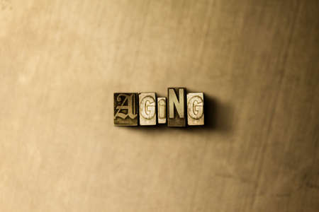 letterpress type: AGING - close-up of grungy vintage typeset word on metal backdrop. Royalty free stock illustration.  Can be used for online banner ads and direct mail.