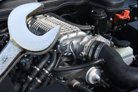 supercharger: Spanner with V8 supercharged car engine in the background