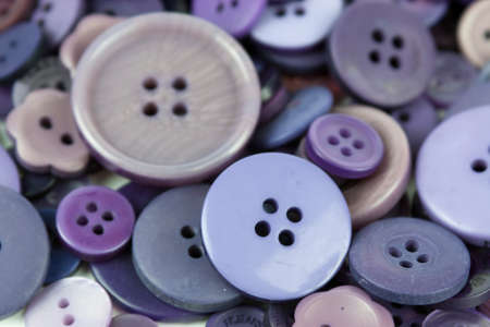Close up of various purple button scattered on a white surface.
