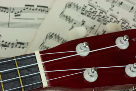 rested: Close up of a ukulele rested on sheet music Stock Photo