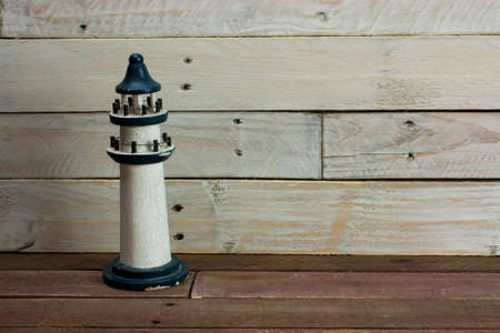 Lighthouse set against a worn wooden background