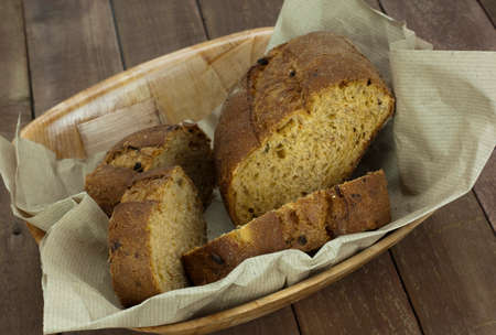 Loaf of wholemeal bread in a basket with brown paper Stock Photo