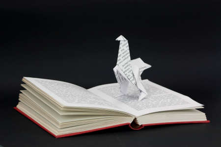 Origami dinosaur with words coming out of a book