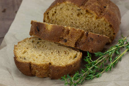 Cut fresh wholemeal bread on a sheet of brown paper Stock Photo