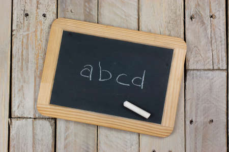 Small blackboard with chalk on a wooden background