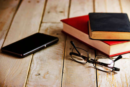Glasses and books on an old wooden surface.