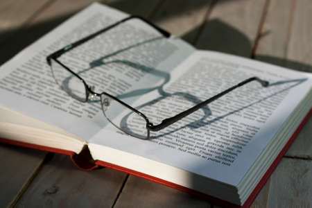 Glasses and books on an old wooden surface. Lorem Ispum text used.
