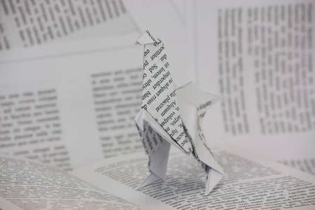 Origami dinosaur with words coming out of a book. Lorem Ipsum text used.