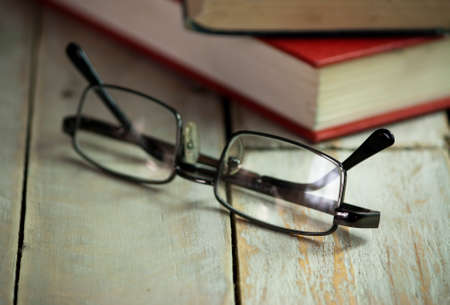 books on a wooden surface: Glasses and books on an old wooden surface