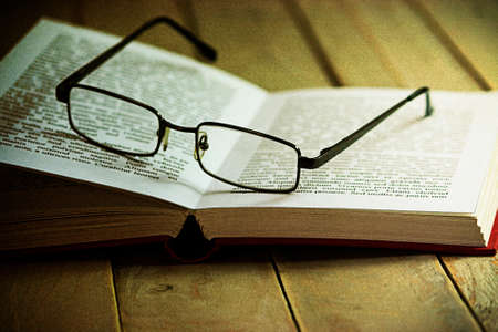 books on a wooden surface: Glasses and books on an old wooden surface. Lorem Ispum text used.  Stock Photo