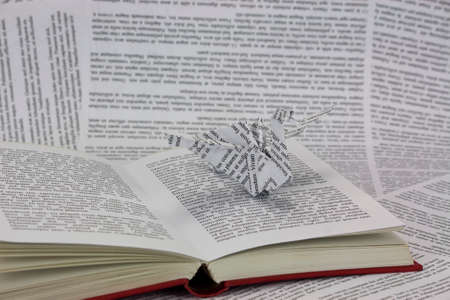 dragon fly: Origami dragon with words coming out of a book.Lorem Ipsum text used. Stock Photo