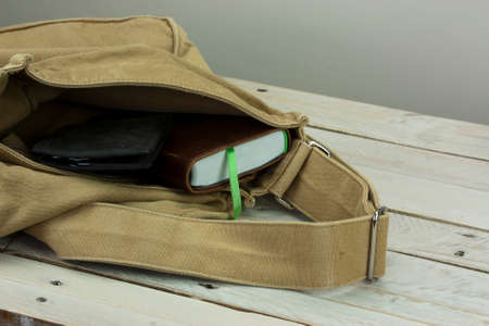opened bag: Wallet and book coming out of an open bag