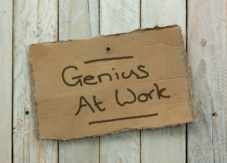 Cardboard sign on a wooden background saying genius at work