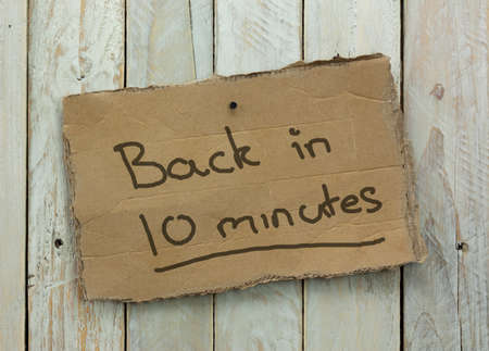 ten empty: Cardboard sign on a wooden background saying back in 10 minutes