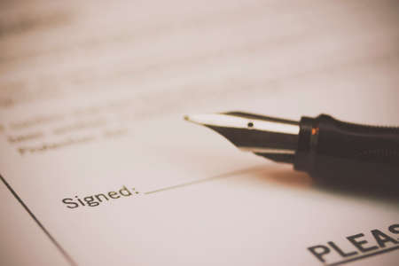 Close up of a fountain pen on a university application form. Retro filter applied.