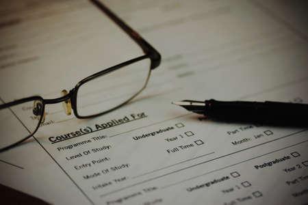 Primer plano de una pluma en un formulario de solicitud a la universidad. Vintage filtro aplicado.