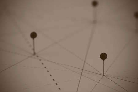 linked: Black pins in paper linked together by lines