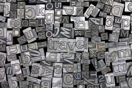 typeset: Close up of old used metal typeset letters with the word travel