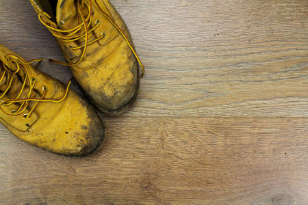 muddy: Muddy work boots on a wooden floor