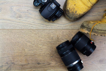 work boots: Muddy work boots and cameraequipment on a wooden floor