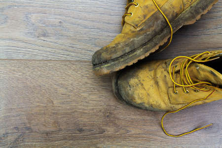 work boots: Muddy work boots on a wooden floor