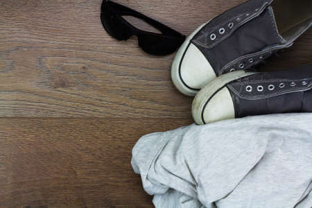 plimsoll: Grey casual shoes and sunglasses on a wooden floor
