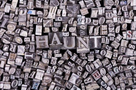 haunt: Close up of old used metal typeset letters with the word haunt Stock Photo