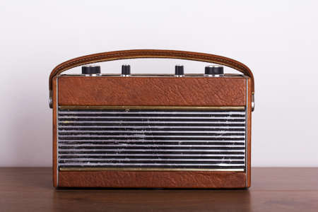 shortwave: Old retro style radio on a wooden surface with light background
