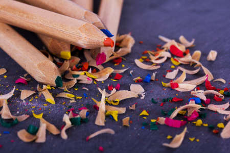 sharpenings: Close-up of coloured pencils on a worn black background