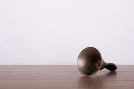 hand bell: Old fashioned hand bell on a wooden surface Stock Photo