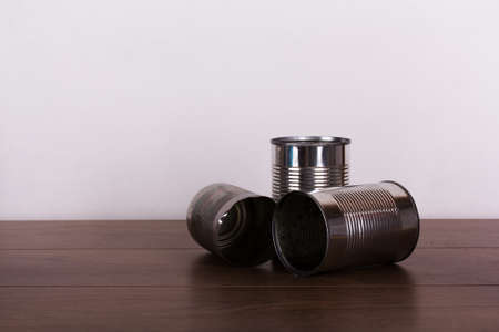 battered: Battered tin cans on a rustic wooden background