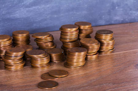 penny: Stack of old penny coins on a wooden surface Stock Photo