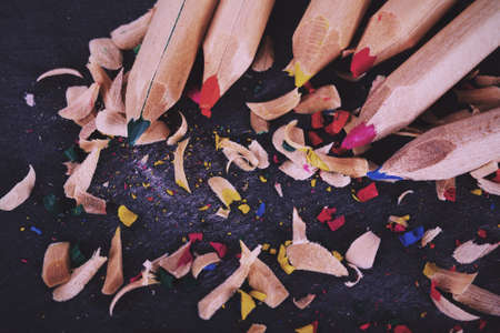 sharpenings: Close-up of coloured pencils on a worn black background Vintage Retro Filter.