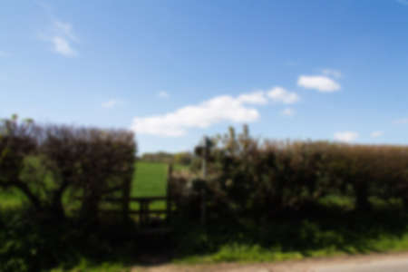stile: Wooden country stile in a hedge leading to field Out of focus. Stock Photo