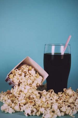 Bucket of popcorn against a blue background Vintage Retro Filter.
